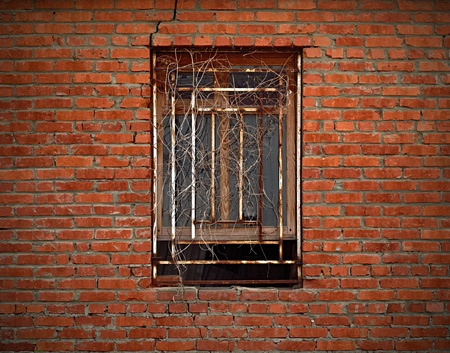 Closed window under rusted grating on aged brick wall  photo