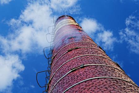 Industrial brick chimney against blue sky Stock Photo