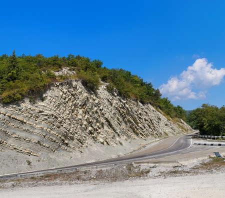 Mountain road. White rock, green trees, blue sky