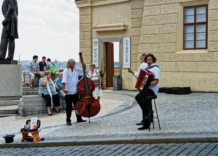 czechoslovak: PRAGUE, CZECH REPUBLIC - AUGUST 5, 2015: Street musicians at Hradcanske Square infront Prague Castle near statue of first Czechoslovak president Tomas Garrigue Masaryk