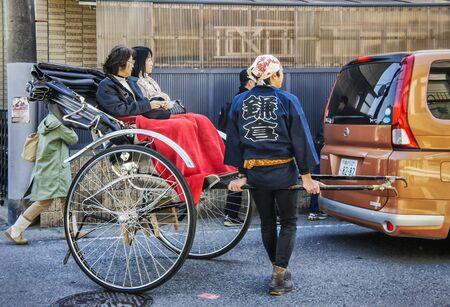 KAMAKURA, JAPAN - APRIL 08, 2012 : Unidentified rickshaw driver with two female passengers in Kamakura, Japan