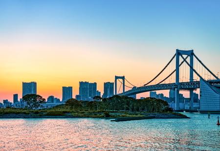TOKYO, JAPAN - OCTOBER 05, 2015: City skyline and Rainbow bridge across Tokyo Bay in sunset. Odaiba, Tokyo, Japan