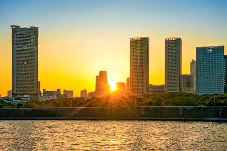 city of sunrise: TOKYO, JAPAN - OCTOBER 05, 2015: City skyline at sunset view from Odaiba over Tokyo Bay, Japan