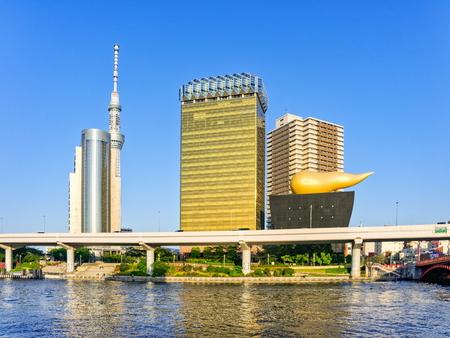 TOKYO, JAPAN - OCTOBER 05, 2015: Landmark buildings line along Sumida River including Asahi Beer Hall with the Golden Flame in Asakusa in Tokyo, Japan