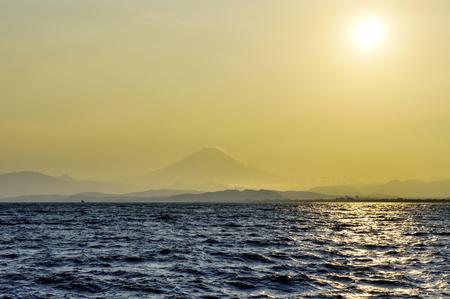 View on Fuji mountain through evening haze over water