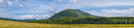 Panorama of Green Hill Landscape with Cloudy Sky Stock Photo