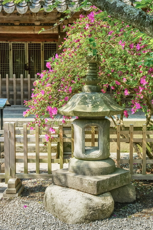 Ancient Japanese stone lantern near traditional Japanese house