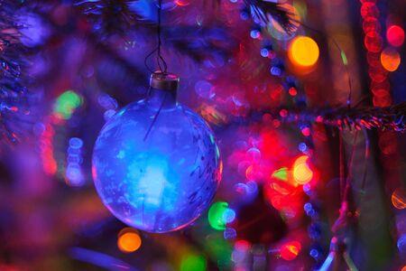 color in: Bola de Navidad en el árbol de Navidad con luces de colores bokeh. El enfoque suave y selectivo