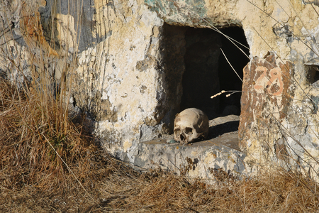 crypt: A human skull at the enter of the crypt. City of the dead: a necropolis near the village of Dargavs, North Ossetia - Alania, Russia