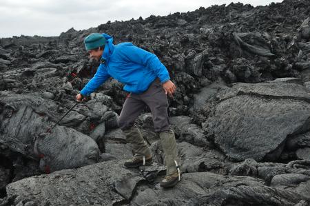 trekking pole: Man sticks the trekking pole into the hot lava flow. New Tolbachik Fissure Eruption (2013), Kamchatka peninsula, Russia
