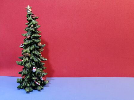 little beautiful christmas tree on christmas eve on blue surface and red background