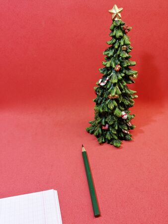 waiting for Christmas night with a pencil for writing wishes on a red background