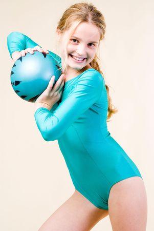 scalzo ragazze: Teenage ginnasta con palla su sfondo grigio