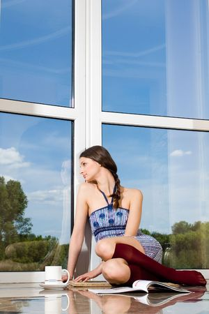 A girl with journal looking throught the window