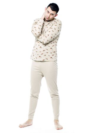 Young man in pajamas on white background