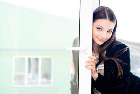 Beautiful woman at window looking at camera