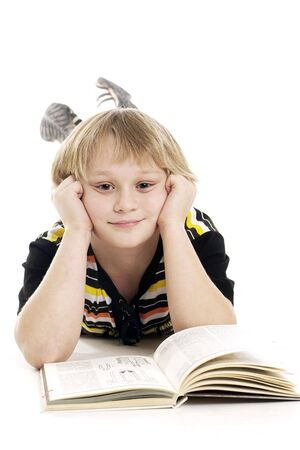 A studio shot of little smiling boy with book