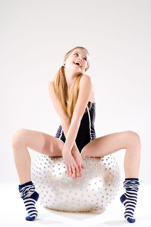 Young pretty positive girl sitting on ball