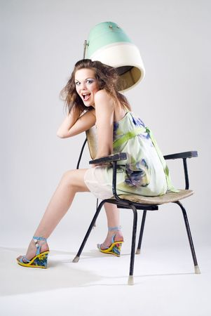 Expressive pretty girl in dress with hair dryer Stock Photo