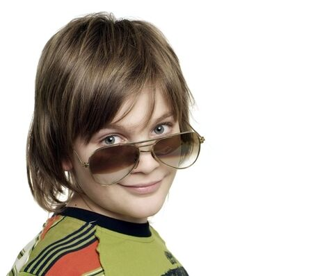 Handsome smiling young boy looking over sunglasses