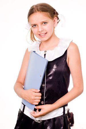 Smiling pretty schoolgirl in dress holding a file Standard-Bild