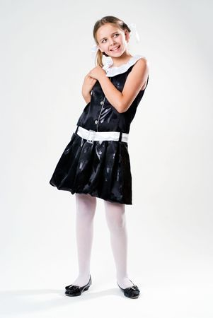 Pretty standing schoolgirl in dress on white background