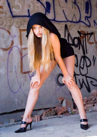 dark haired woman: Beautiful grungy girl posing at graffiti wall