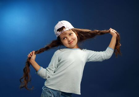 Little funny girl posing at blue background