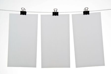 Three blank sheets of paper hanging on rope