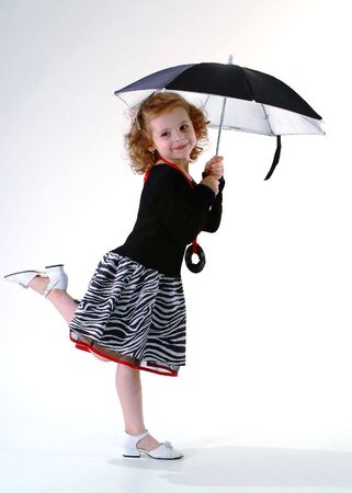 Pretty little girl standing under black umbrella