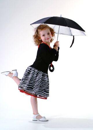 Pretty little girl standing under black umbrella