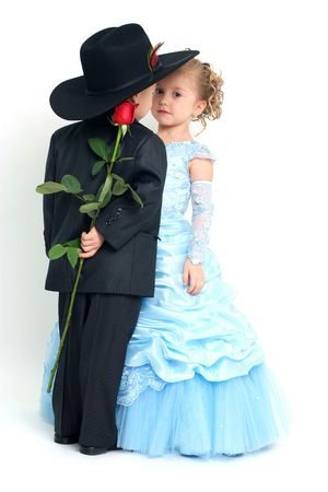 little boy and girl: Lovely girl and boy hiding a rose behind his back Stock Photo