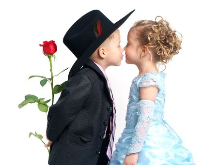 Little pretty boy with rose kisses girl in blue dress Stock Photo