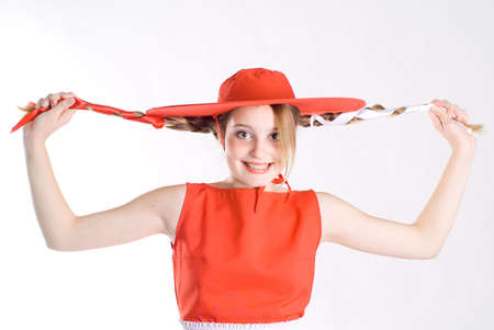 Joking girl with pigtails in red hat photo