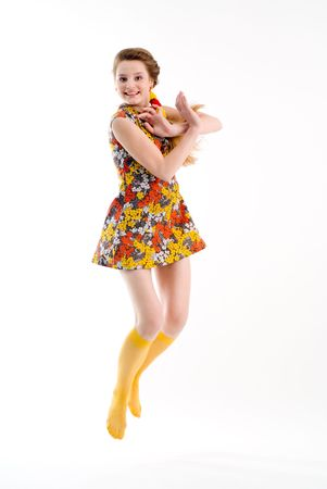 Funny jumping girl in dress and yellow stockings Standard-Bild