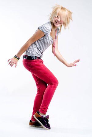 punk hair: Funky teenage blonde emo girl dancing at white background