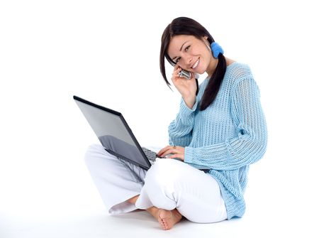 Brunette talking at a cellphone and working at laptop photo
