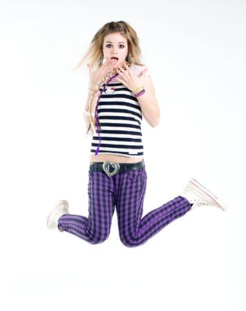 Shocked jumping teenage trendy girl studio shot photo
