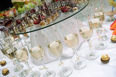 served: Row of glasses of white wine and sweets Stock Photo