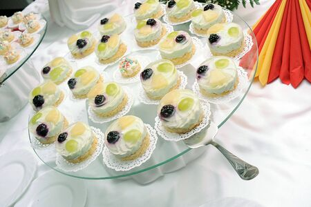 Tasty round jelly cakes with fruits on the plate photo