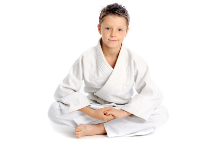 Young karate boy sitting in lotus pose photo
