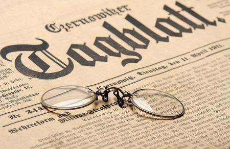 old english: Vintage eyeglasses over old newspaper background Stock Photo