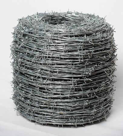 barb wire isolated: Roll of twisted barbed wire at white background