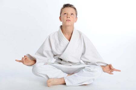 Young karate boy sitting in lotus pose