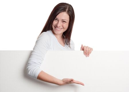 Girl pointing with hand on a huge blank white sheet of paper Standard-Bild