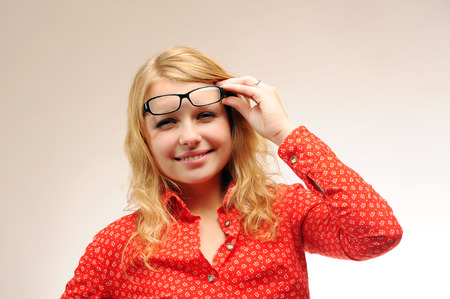 Pretty blonde girl with poor eyesight posing removing glasses and squints