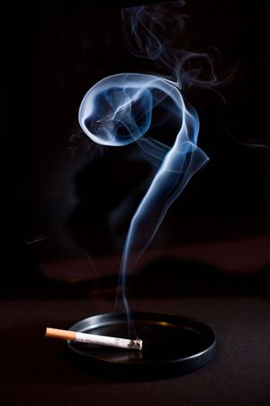 Cigarette and smoke as questionmark on black background  photo