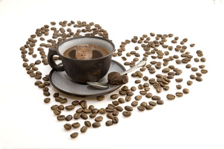 Cup of coffee and the heart shape made from beans photo