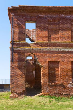 Old red brick broken building at sunny summer day