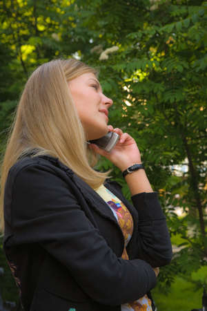 Young blonde lady talking with mobile phone in her hand